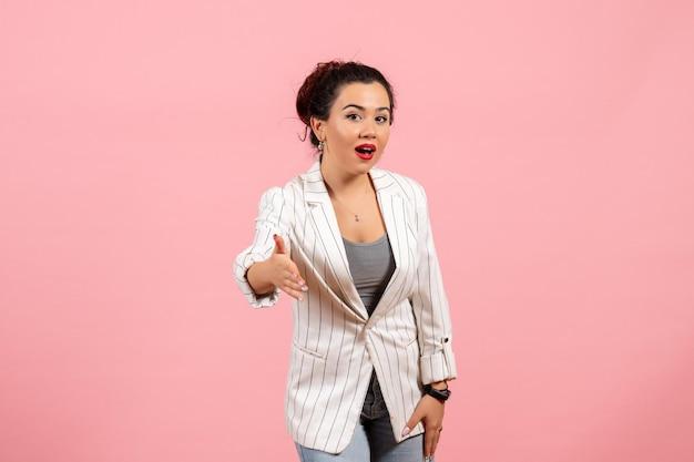 Vue de face jeune femme avec une veste blanche essayant de serrer la main sur fond rose lady fashion femme émotions couleur