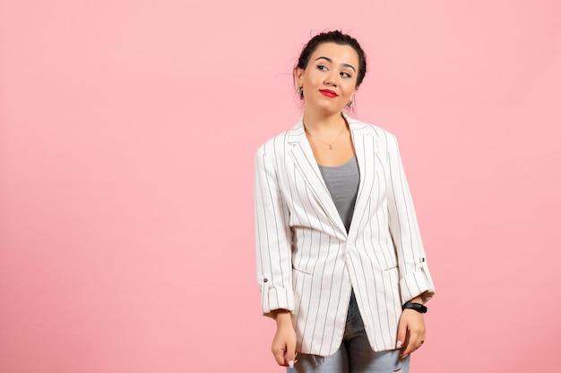 Vue de face jeune femme avec une veste blanche juste debout sur fond rose émotions dame mode sentiment femme couleur