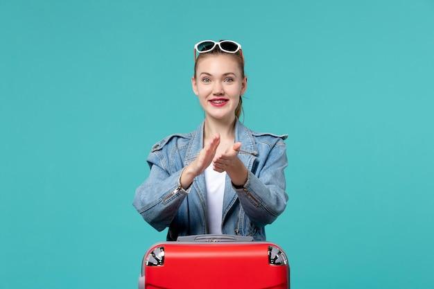 Vue de face jeune femme en veste bleue se prépare pour le voyage applaudissant sur l'espace bleu