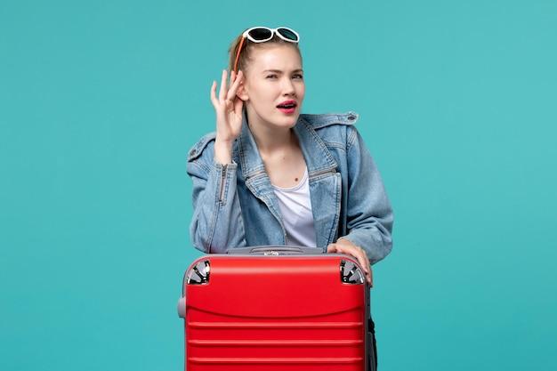 Vue de face jeune femme en veste bleue se prépare pour le voyage et essaie d'entendre sur l'espace bleu