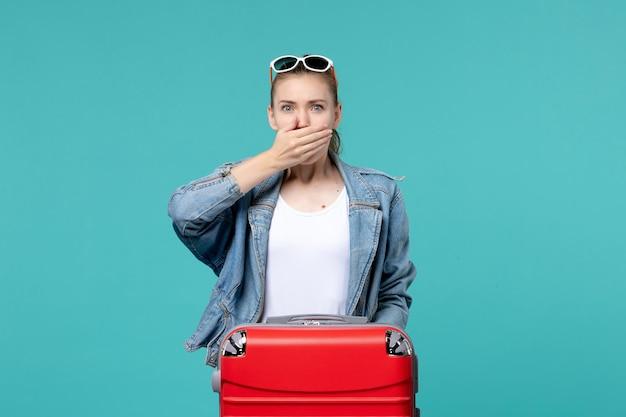 Vue de face jeune femme en veste bleue se prépare pour le voyage avec une expression surprise sur l'espace bleu