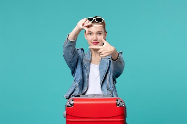 Vue de face jeune femme en veste bleue se prépare pour le voyage posant sur l'espace bleu