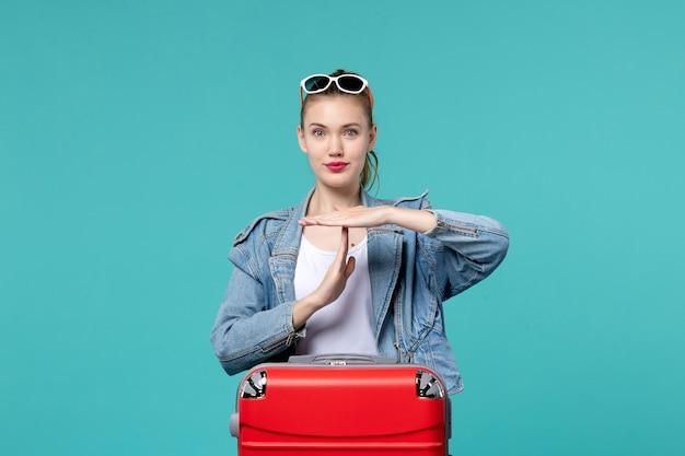 Vue de face jeune femme en veste bleue se prépare pour le voyage showign signe t sur l'espace bleu