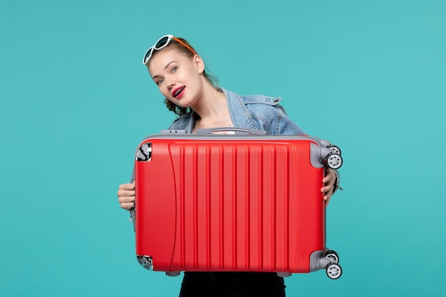 Vue de face jeune femme en veste en jean tenant son sac rouge sur l'espace bleu clair