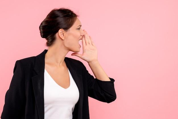 Vue de face jeune femme en veste sombre appelant fort sur fond rose