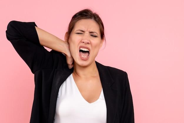Vue de face jeune femme en veste sombre ayant des douleurs au cou sur fond rose