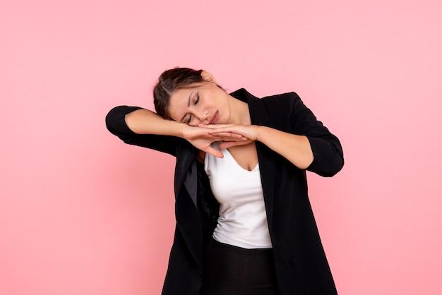 Vue de face jeune femme en veste sombre avec bras blessé sur fond rose