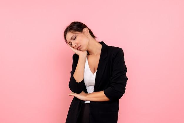 Vue de face jeune femme en veste sombre dormant sur fond rose