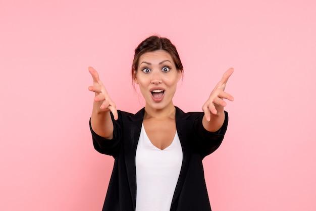 Vue de face jeune femme en veste sombre excitée sur fond rose