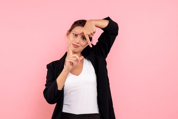 Vue de face jeune femme en veste sombre sur fond rose