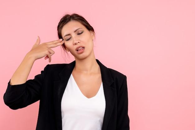 Vue de face jeune femme en veste sombre mettant ses doigts dans sa tempe sur fond rose