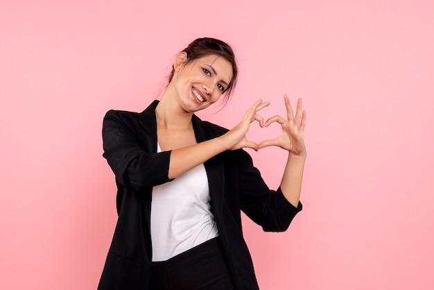 Vue de face jeune femme en veste sombre montrant signe d'amour sur fond rose