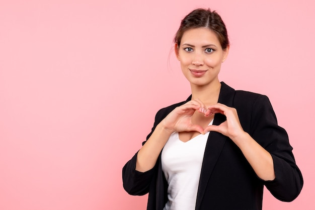 Vue de face jeune femme en veste sombre montrant le signe du coeur sur fond rose
