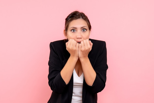 Vue de face jeune femme en veste sombre nerveuse sur fond rose