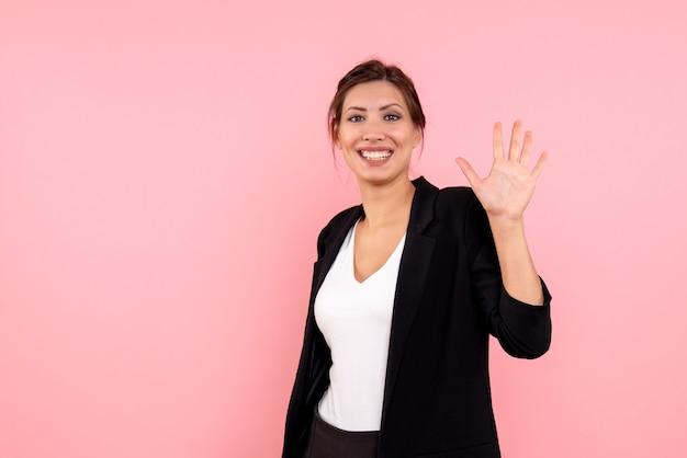 Vue de face jeune femme en veste sombre salutation et souriant sur fond rose
