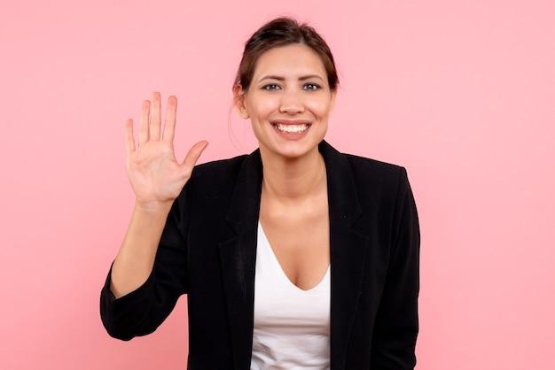 Vue de face jeune femme en veste sombre salutation avec sourire sur fond rose