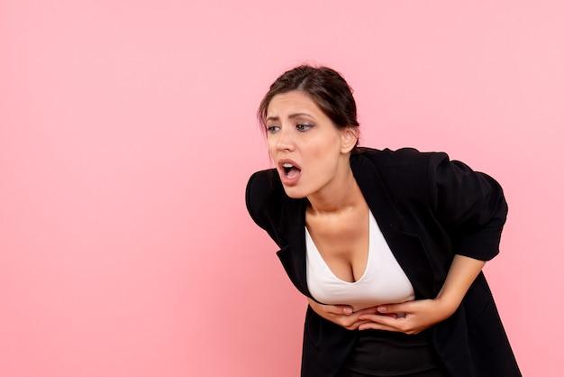 Vue de face jeune femme en veste sombre souffrant de maux d'estomac sur fond rose