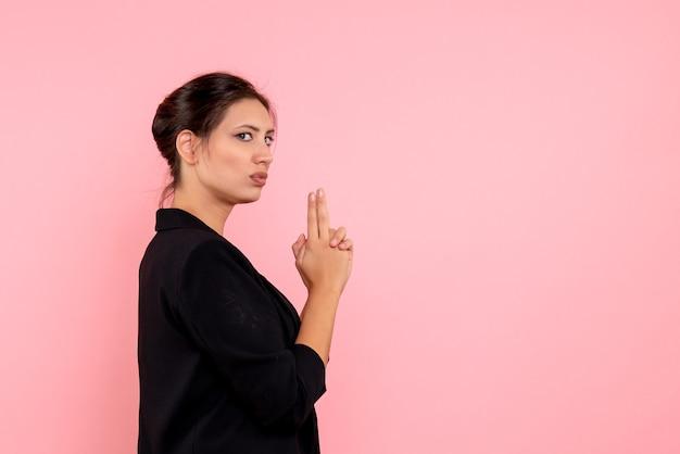 Vue de face jeune femme en veste sombre en tenue de pistolet pose sur fond rose
