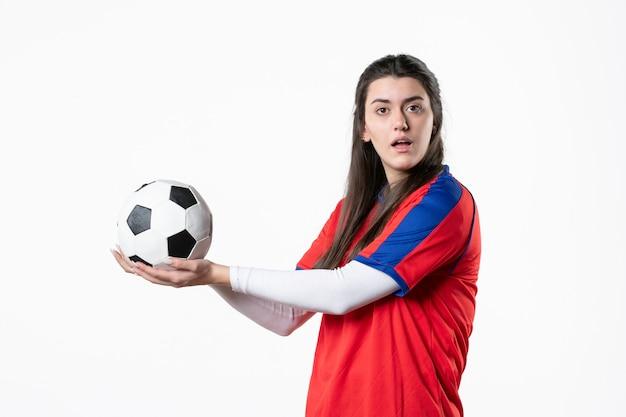 Vue de face jeune femme en vêtements de sport avec ballon de foot sur mur blanc