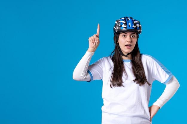 Vue de face jeune femme en vêtements de sport avec casque sur mur bleu