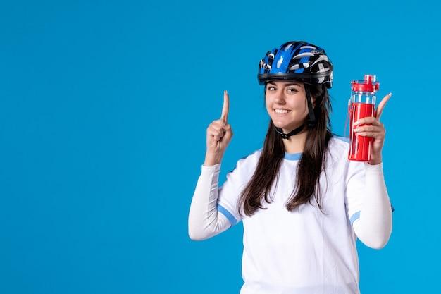 Vue de face jeune femme en vêtements de sport et casque sur mur bleu