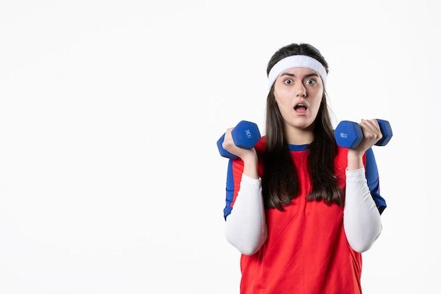 Vue de face jeune femme en vêtements de sport avec des haltères bleus sur un mur blanc