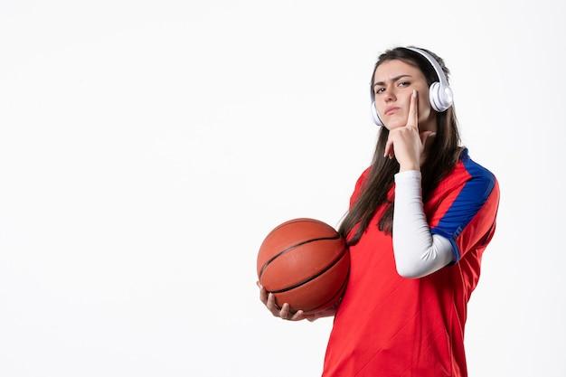 Vue de face jeune femme en vêtements de sport avec mur blanc de basket-ball