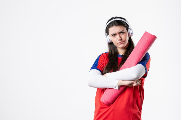 Vue de face jeune femme en vêtements de sport avec tapis de yoga, écouter de la musique mur blanc