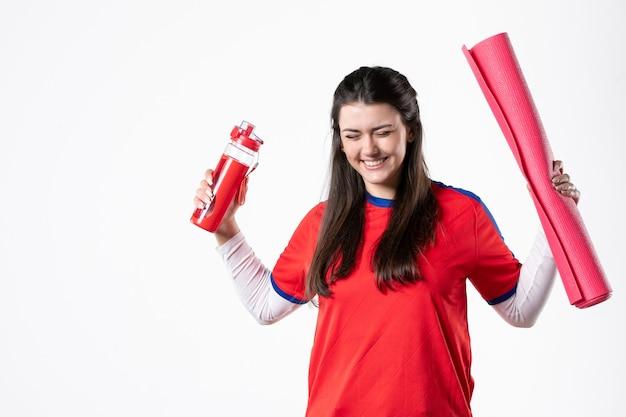 Vue de face jeune femme en vêtements de sport avec tapis de yoga mur blanc