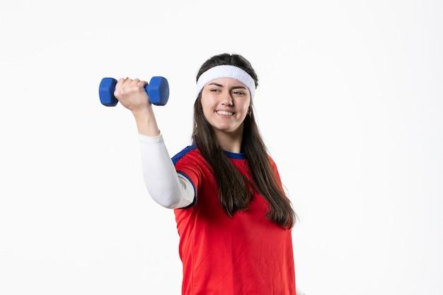Vue de face jeune femme en vêtements de sport travaillant avec des haltères sur un mur blanc