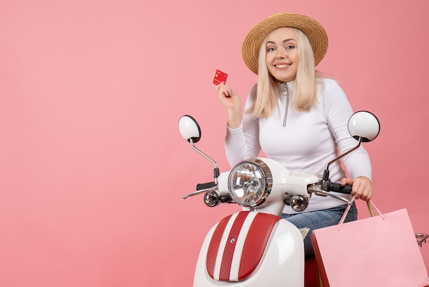 Vue de face jeune femme avec visage heureux sur carte de tenue de cyclomoteur