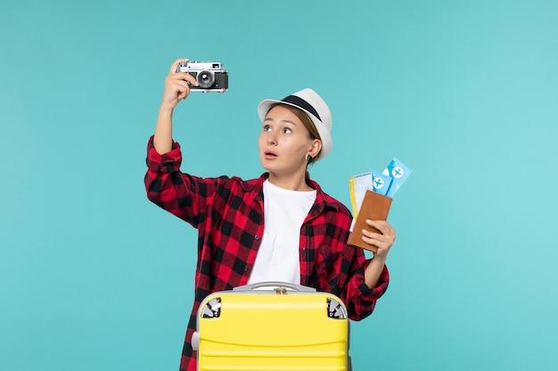 Vue de face jeune femme en voyage tenant des billets et un appareil photo sur un bureau bleu