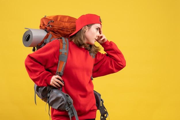 Vue de face jeune femme voyageur avec sac à dos mettant la main sur son visage