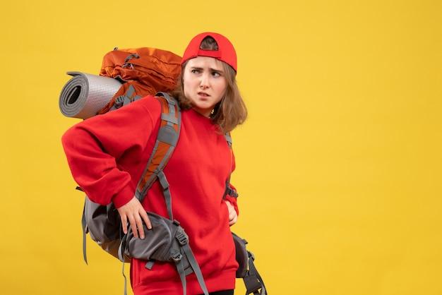 Vue de face jeune femme voyageur avec sac à dos mettant les mains sur une taille