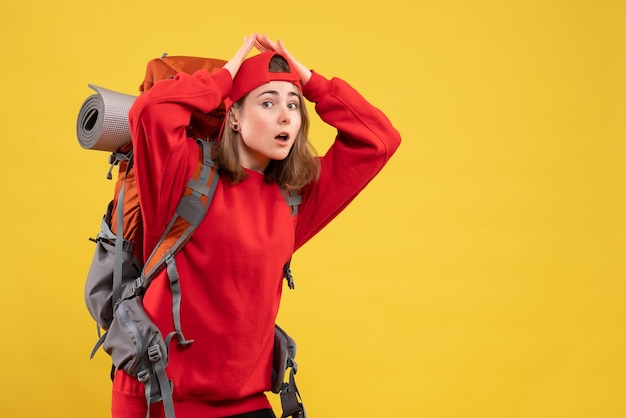 Vue de face jeune femme voyageur en sac à dos rouge joignant les mains au-dessus de sa tête debout sur le mur jaune