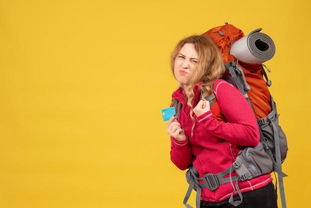Vue de face de jeune fille ambitieuse voyageant dans un masque médical tenant une carte bancaire
