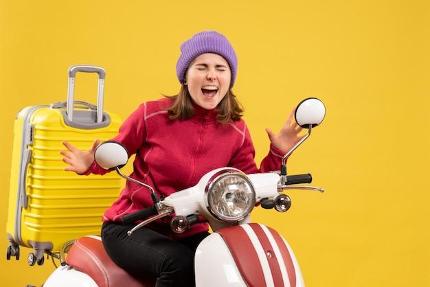 Vue de face jeune fille au chapeau violet sur un cyclomoteur exprimant ses sentiments