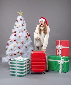 Vue de face jeune fille blonde tenant valise rouge