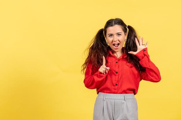 Vue de face jeune fille en blouse rouge avec des cheveux mignons et une drôle de tête sur fond jaune innocence enfant fille jeunesse couleur enfant