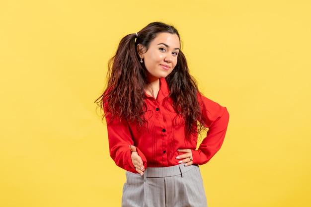 Vue de face jeune fille en blouse rouge avec des cheveux mignons essayant de serrer la main sur fond jaune innocence enfant fille jeunesse couleur enfant