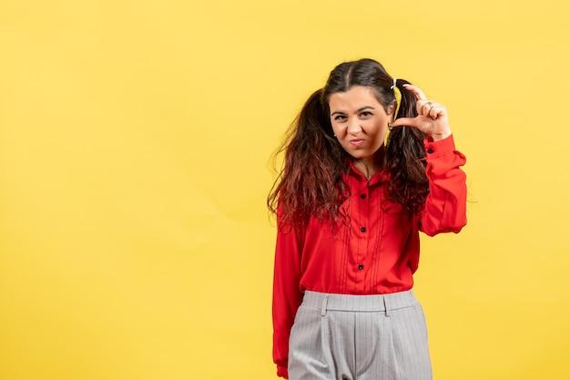 Vue de face jeune fille en blouse rouge avec des cheveux mignons montrant la taille sur fond jaune innocence enfant fille jeunesse couleur enfant