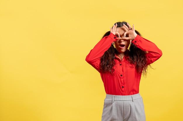 Vue de face jeune fille en blouse rouge avec des cheveux mignons posant sur un bureau jaune enfant fille jeunesse innocence couleur enfant