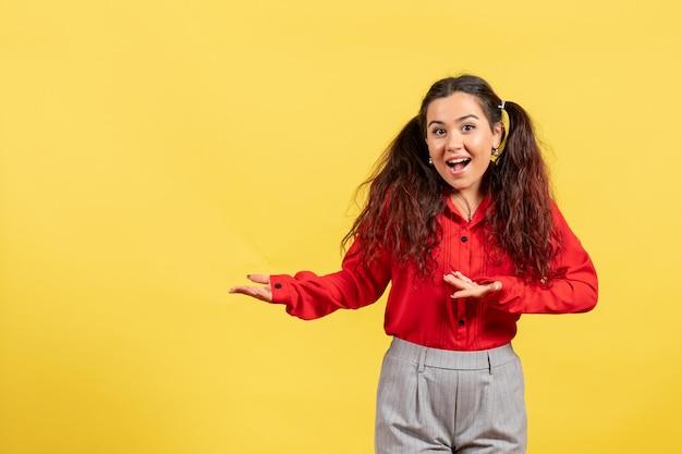 Vue de face jeune fille en blouse rouge avec des cheveux mignons posant sur fond jaune enfant fille jeunesse innocence couleur enfant