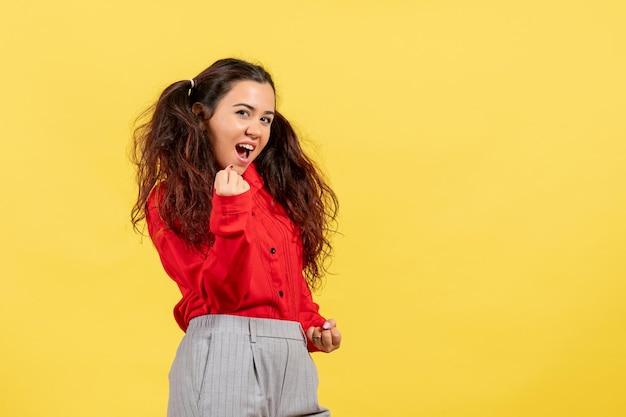 Vue de face jeune fille en blouse rouge avec des cheveux mignons se réjouissant sur fond jaune couleur enfant enfant fille jeunesse innocence