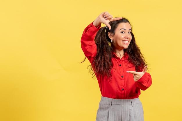 Vue de face jeune fille en blouse rouge avec des cheveux mignons souriant sur fond jaune innocence enfant fille jeunesse couleur enfant