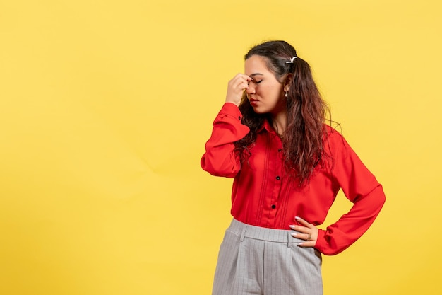 Vue de face jeune fille en blouse rouge avec des cheveux mignons et visage blessé sur fond jaune innocence enfant fille jeunesse couleur enfant