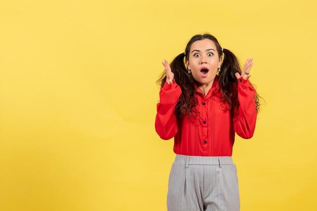 Vue de face jeune fille en blouse rouge avec des cheveux mignons et un visage choqué sur fond jaune innocence enfant fille jeunesse couleur enfant