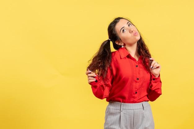 Vue de face jeune fille en blouse rouge avec des cheveux mignons et visage coquette sur fond jaune innocence enfant fille jeunesse couleur enfant