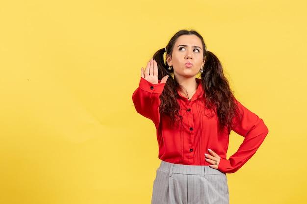 Vue de face jeune fille en blouse rouge avec des cheveux mignons et un visage de rêve sur fond jaune innocence enfant fille jeunesse couleur enfant
