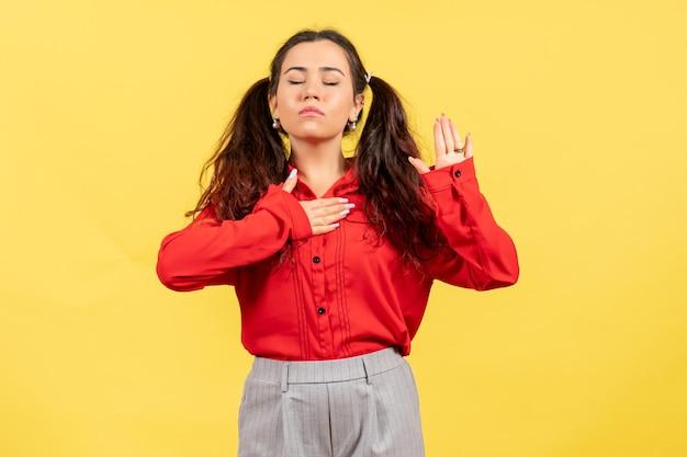 Vue de face jeune fille en blouse rouge avec expression de rêve sur fond jaune sentiment féminin enfant fille jeunesse émotion